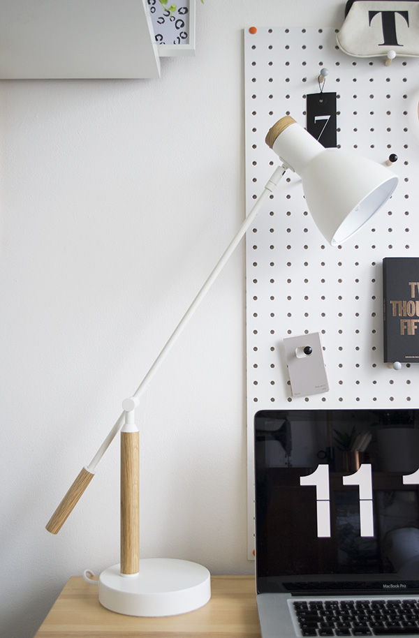 Minimal workspace featuring white PegBoard from Block and white 'Cohen' white desk lamp by MADE.COM.