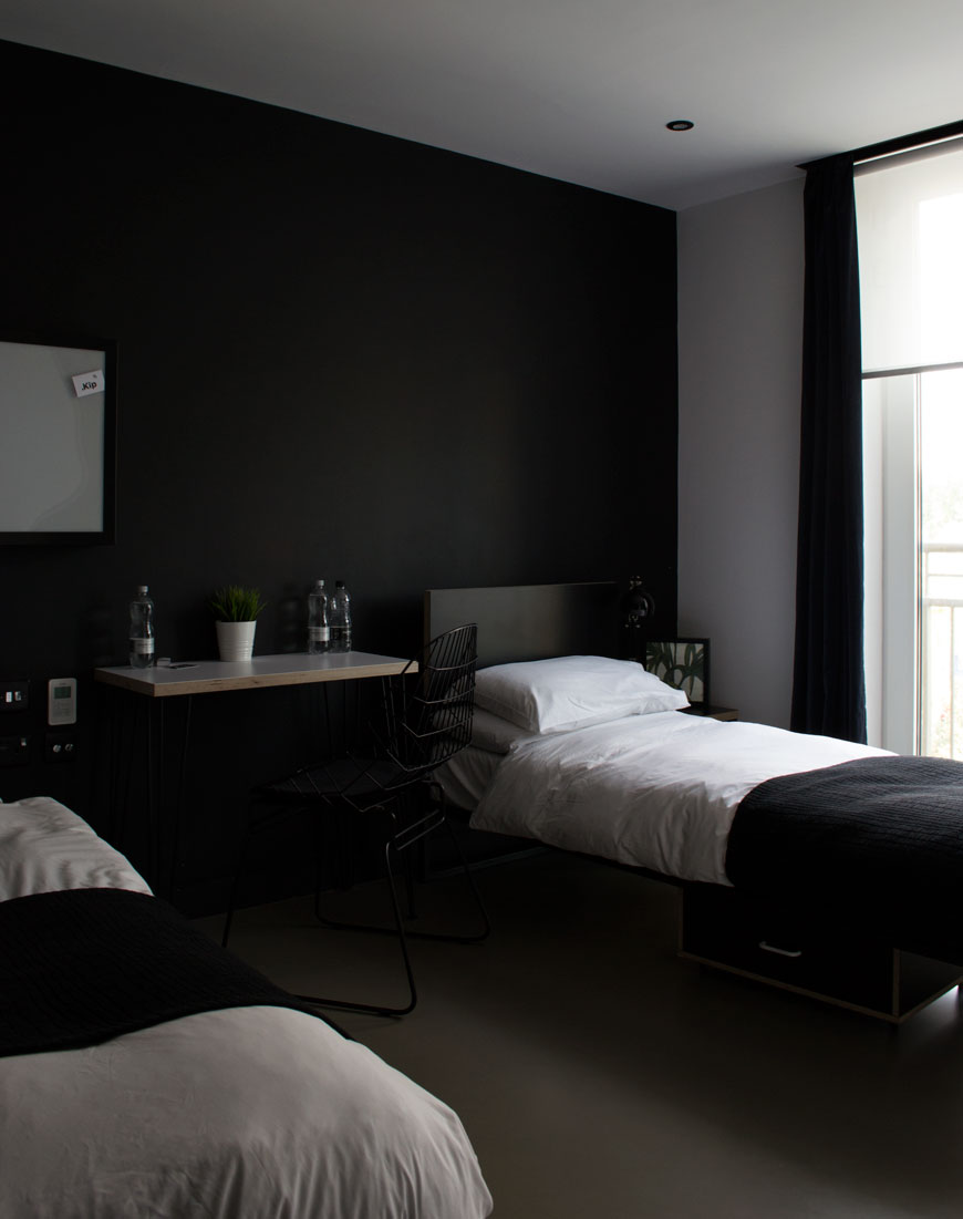 Black painted walls with white bedsheets at Kip Hotel, London