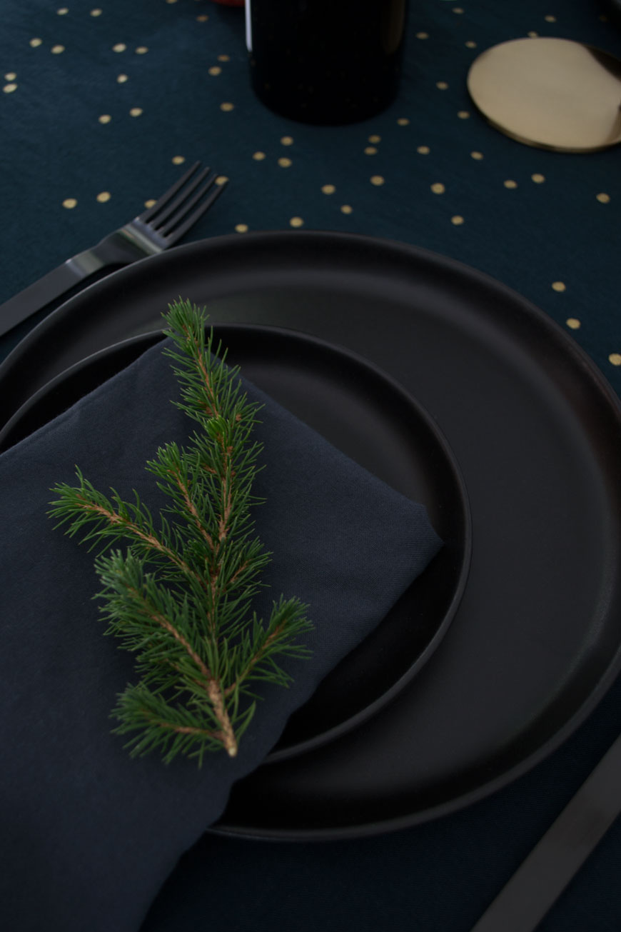 Using black kitchen dinner plates to create a moody and minimal Christmas table setting topped with winter foliage
