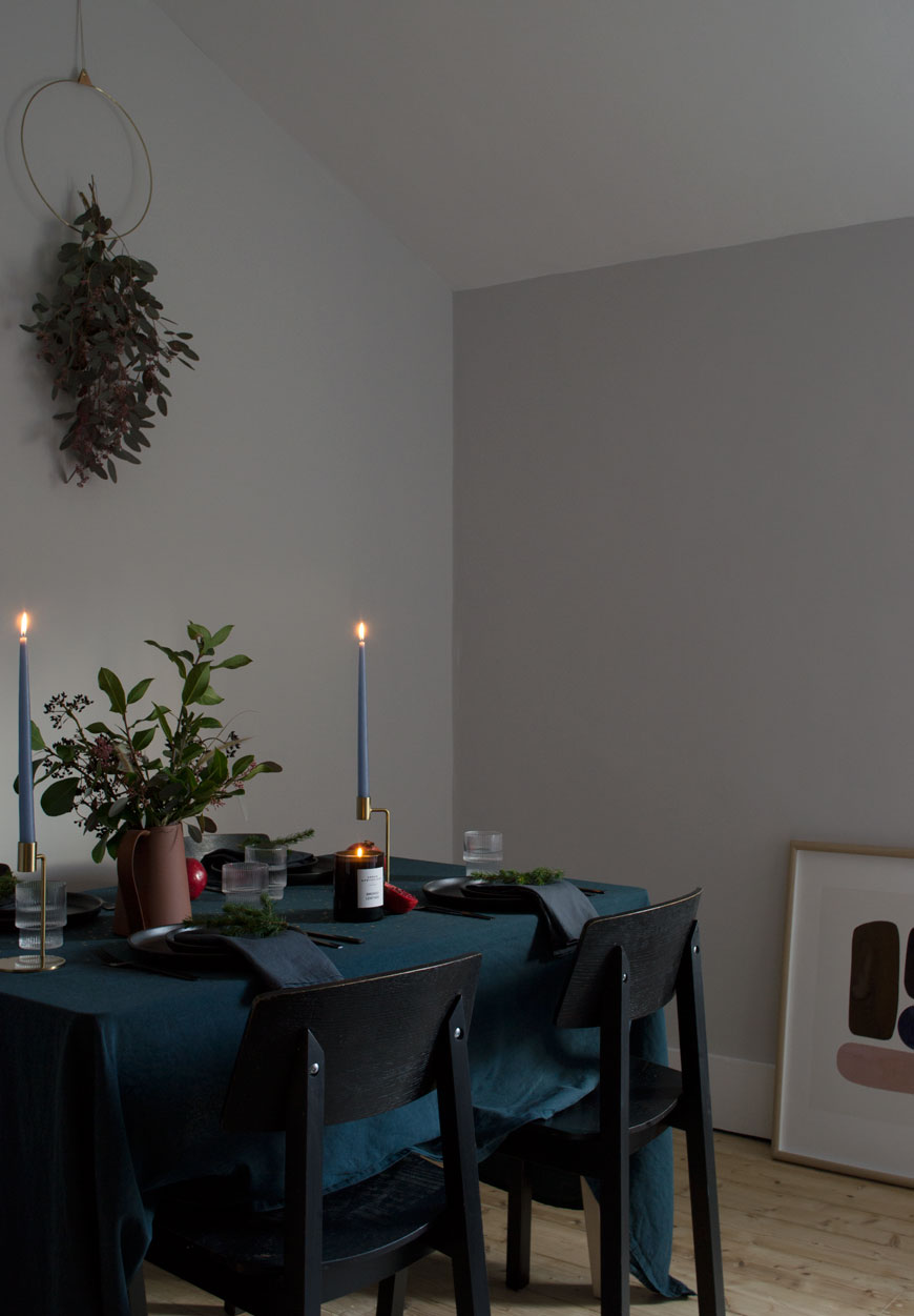 Moody and minimal Christmas table styling with a blue table cloth, black dinner plates and natural winter foliage