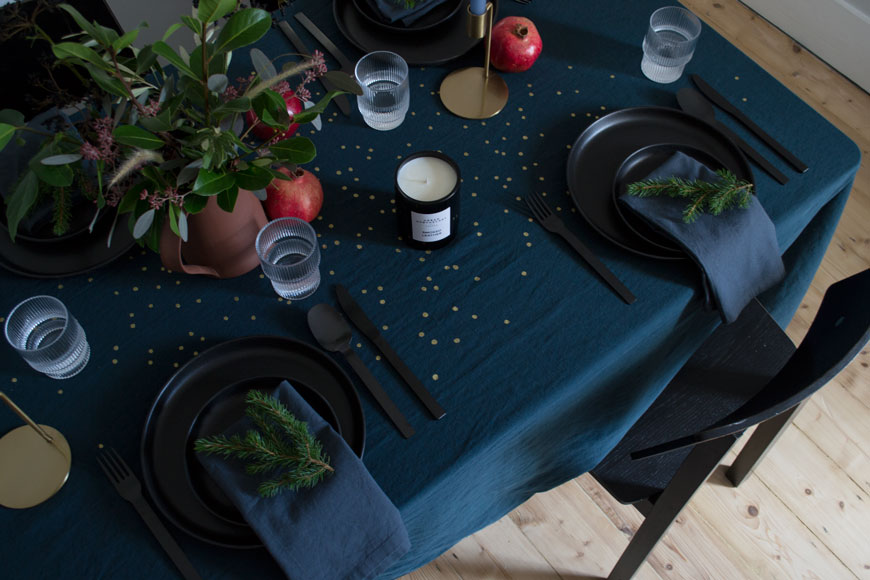 Moody and minimal Christmas table inspired by the Nordic design scene featuring deep blue table linen from La Cerise sur le gateau