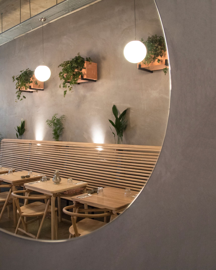 London restaurant Amber in Aldgate East, contemporary modern design, ash dining furniture designed by Charles Dedman, bare plaster walls, large round mirrors, hanging plants