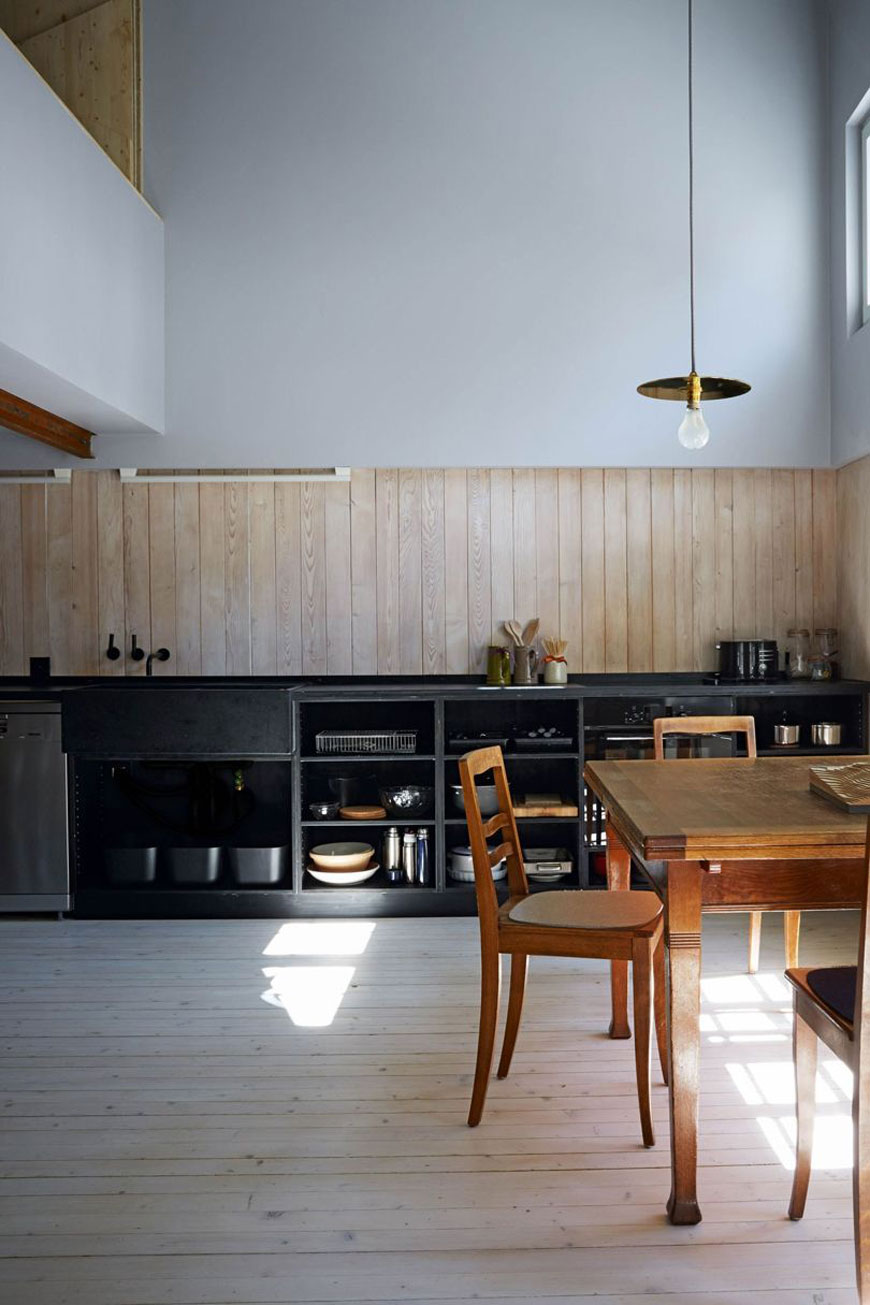 unique architectural holiday home experience, swiss chalet Halb Haus designed by Jonathan Tuckey, large open plan kitchen with mezzanine, tall ceilings