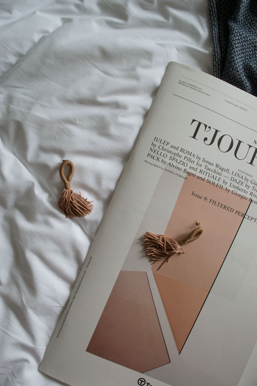 Lifestyle shot of a newspaper and tassel earrings on the bed at The Good Hotel London,