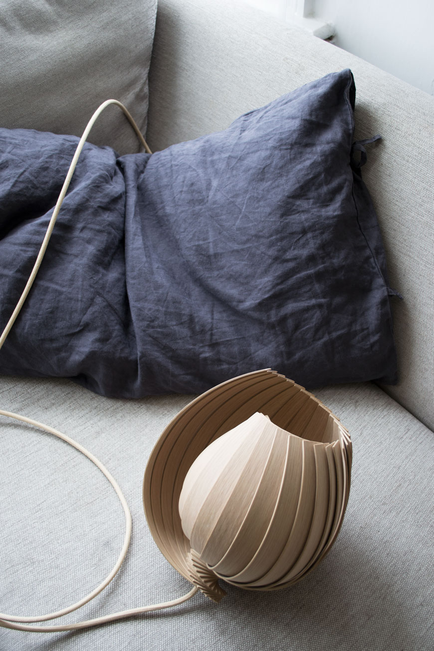 L25 Lamp designed by Kovac Family from sustainable oak, blue linen cushion on a grey sofa