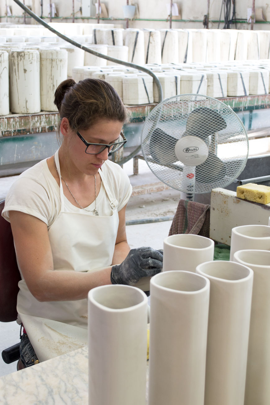 A factory worker removing imperfections from ceramic vases with a wet sponge in a ceramics factory in Portugal.