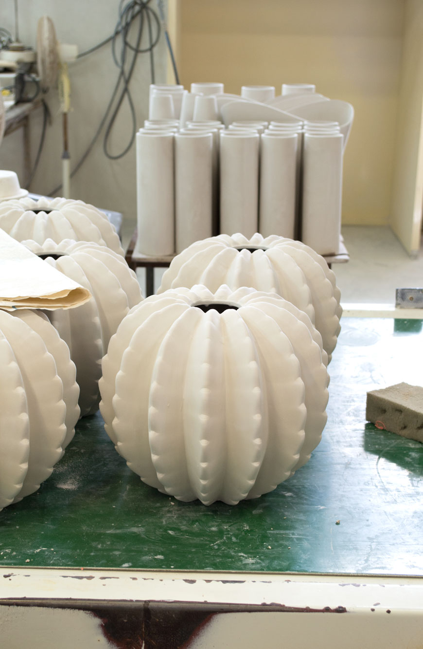 White ceramic cactus vases sit drying on a tabletop inside a ceramics factory in Portugal