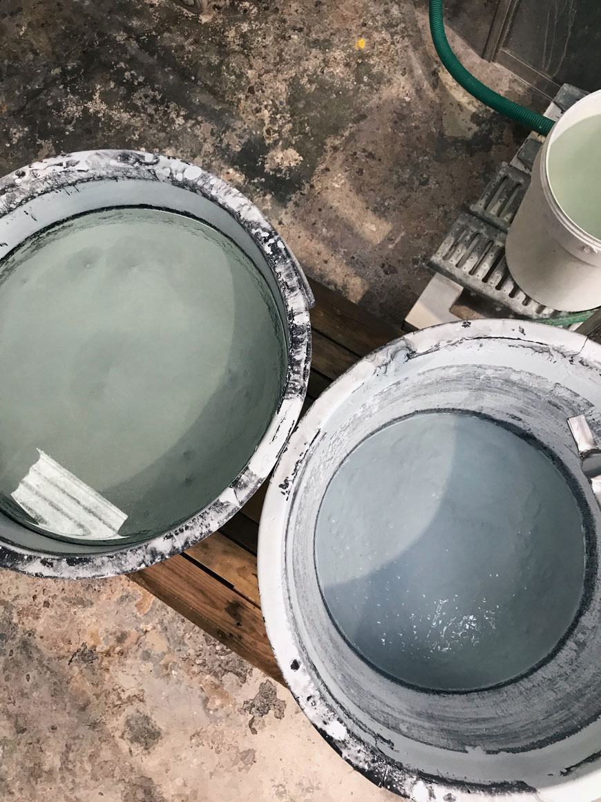 A bucket of green and blue ceramic glaze inside a ceramics factory in Portugal