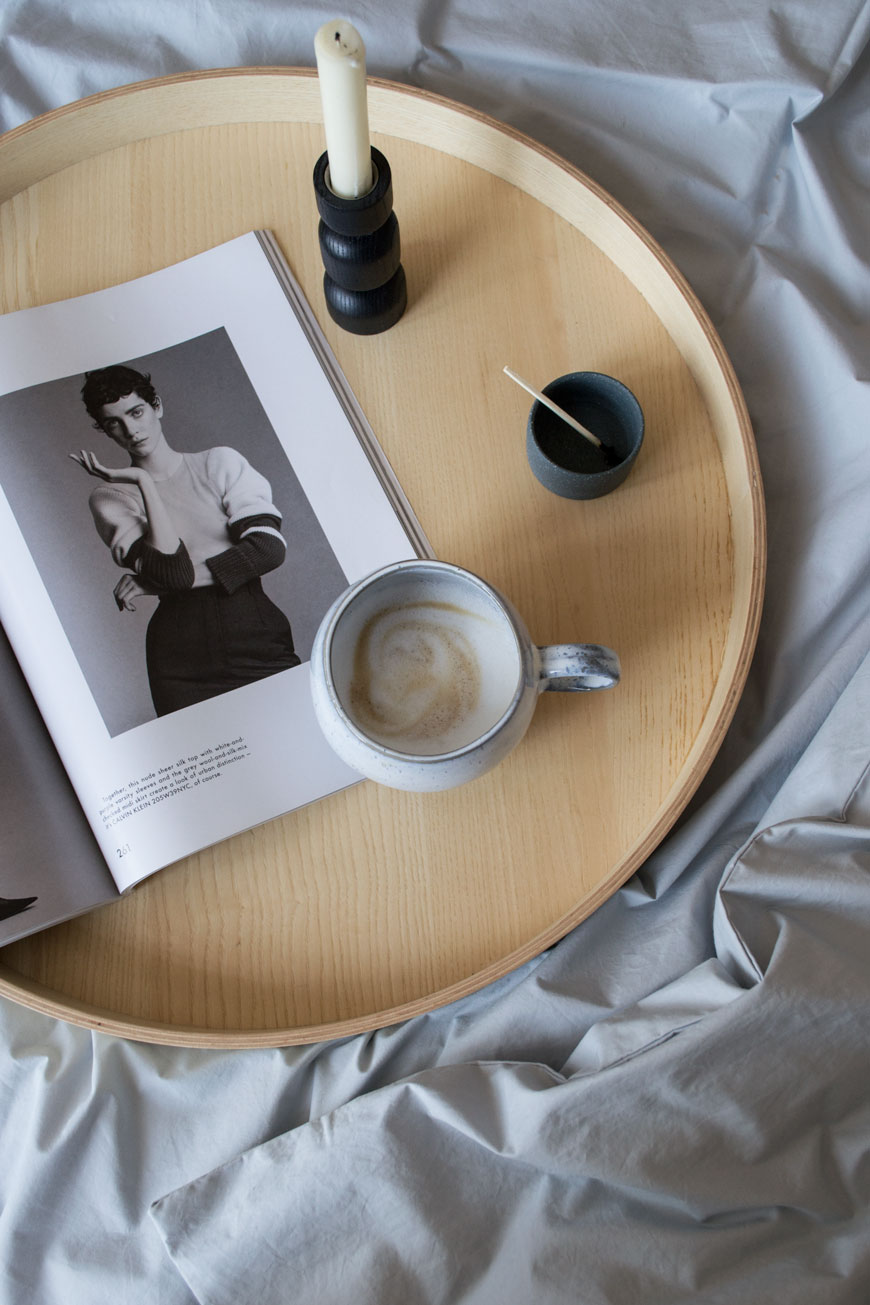 round wooden tray with a cup of coffee and a magazine on cotton sheets on the bed