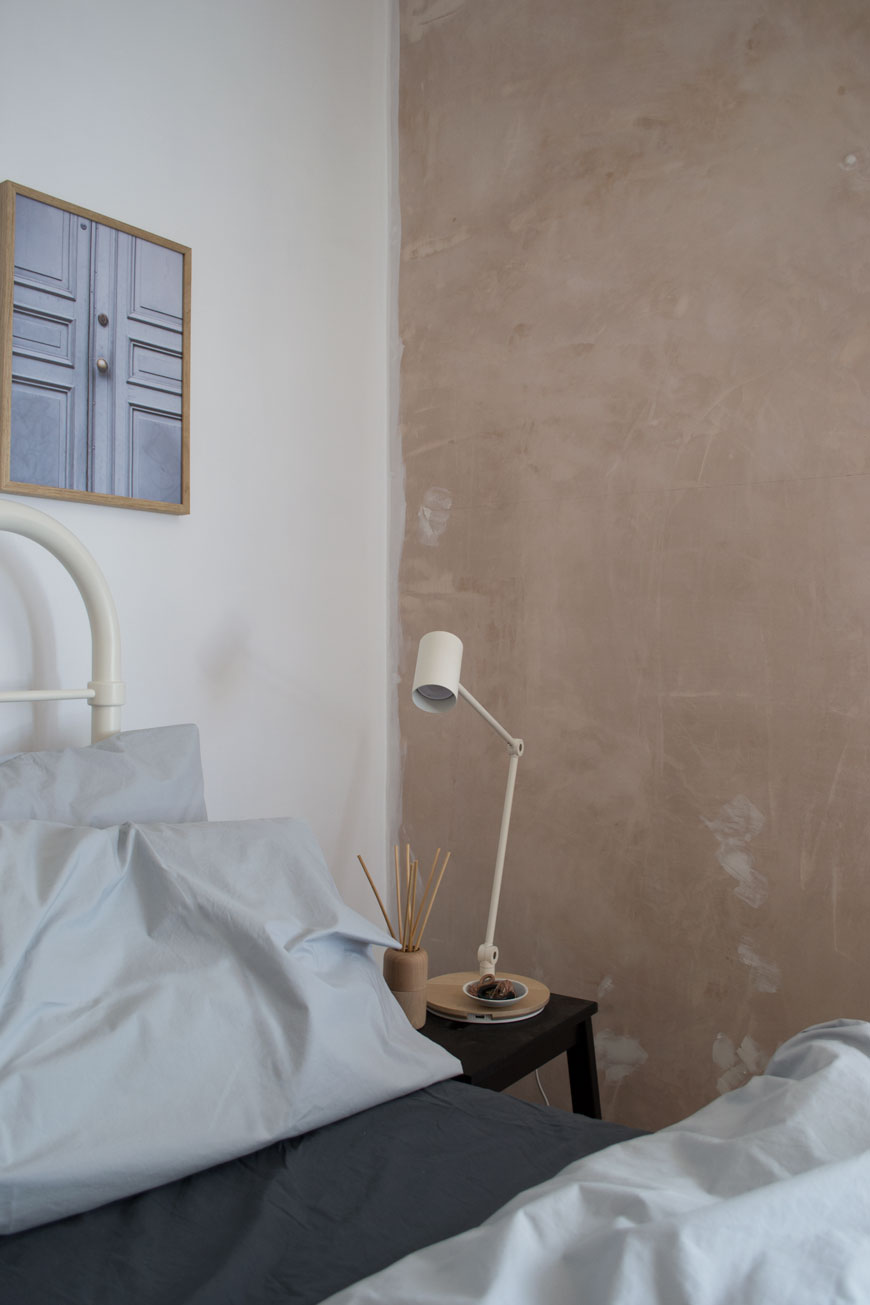 A white bedside lamp in a bedroom with light and dark grey cotton sheets on the bed
