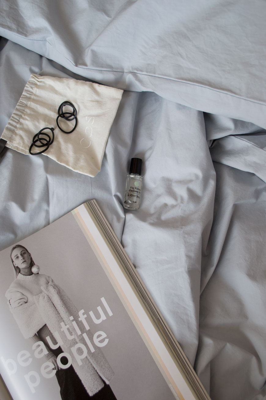 A fashion magazine, black metal earrings and perfume on light grey cotton sheets