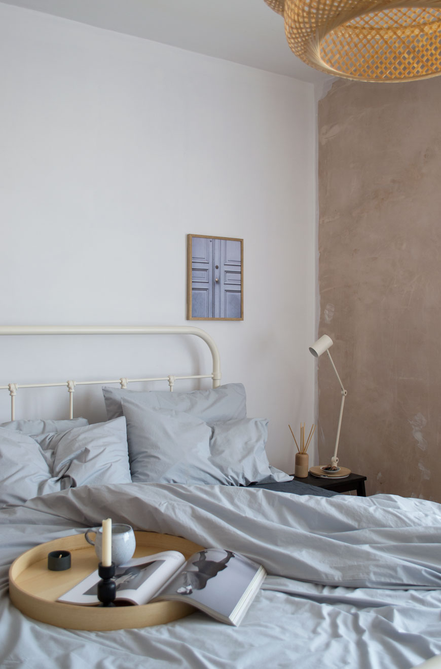 light bedroom with white and plaster pink walls and grey cotton sheets