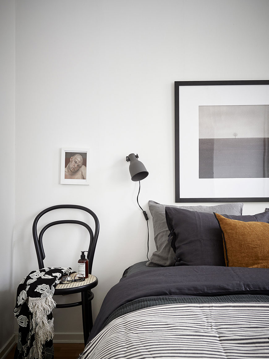 Black framed art and black wall lamp in a minimalist white bedroom with a black bentwood chair for a bedside table.