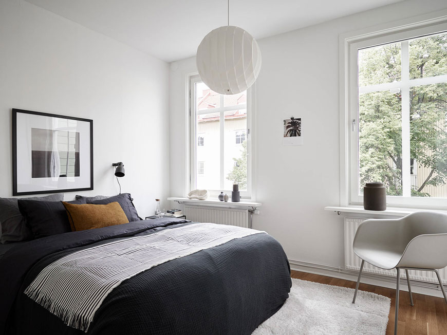 Minimalist white bedroom with dark blue and grey linen bedding in a Gothenburg apartment.