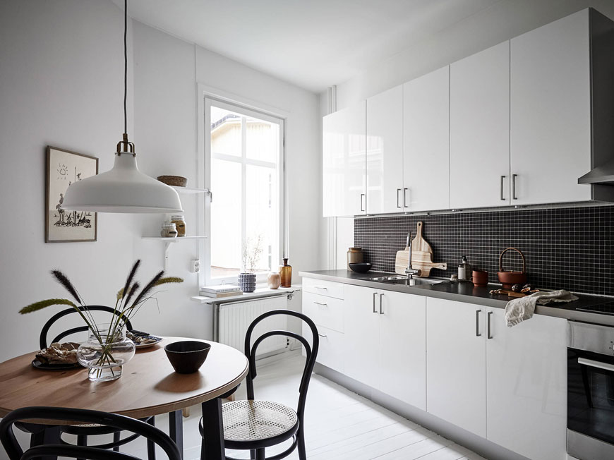 A black and white monochrome kitchen in Gothenburg with a small round table and black Thonet cane chairs and black mosaic splashback.