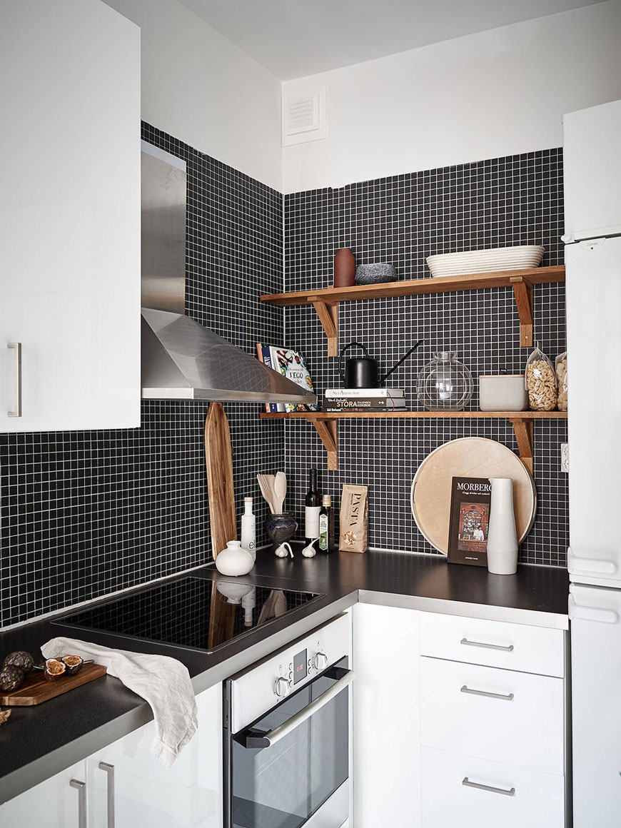Black mosaic tiled wall in a monochrome kitchen with open wooden shelves, high gloss white units and bags of pasta