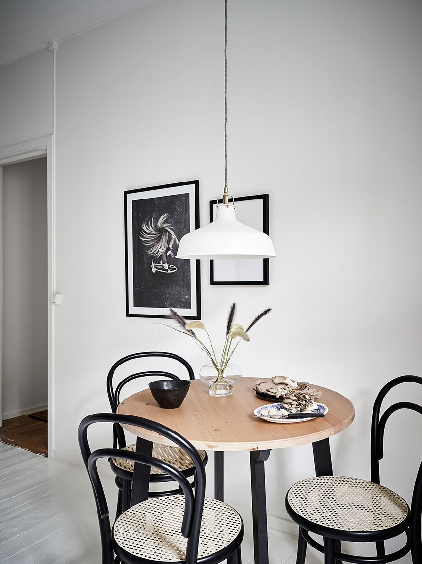 Three black cane Thonet bentwood chairs around a round table in a kitchen.
