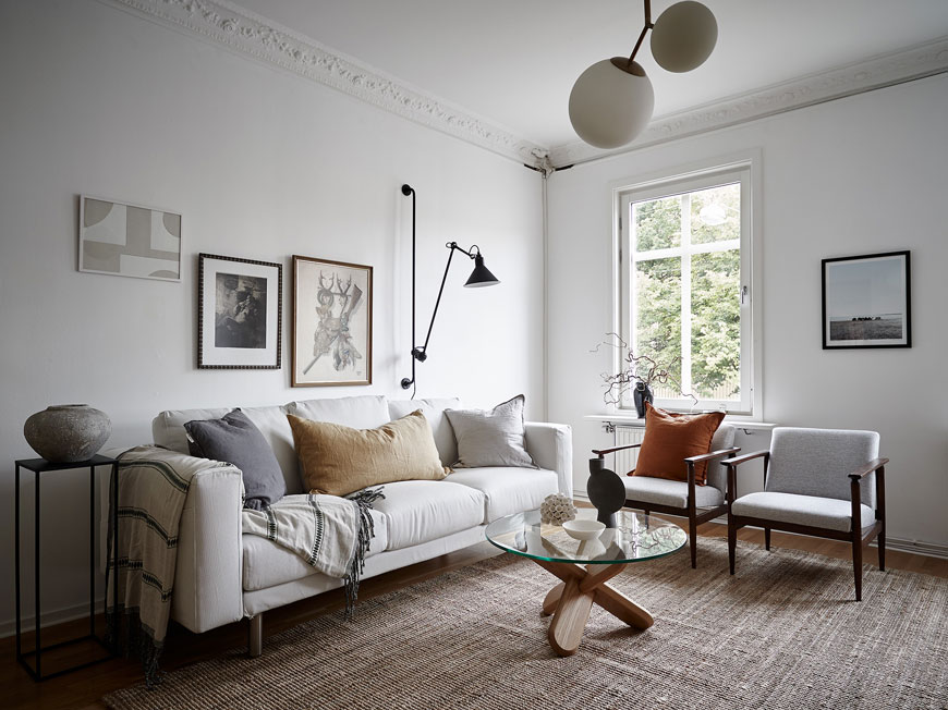 White living room with white sofa, rattan rug and two grey Mid-Century chairs in an apartment
