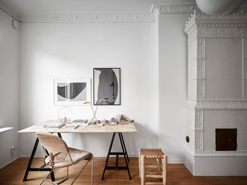 Chipboard desk on black trestles in a white living room in a Gothenburg apartment.