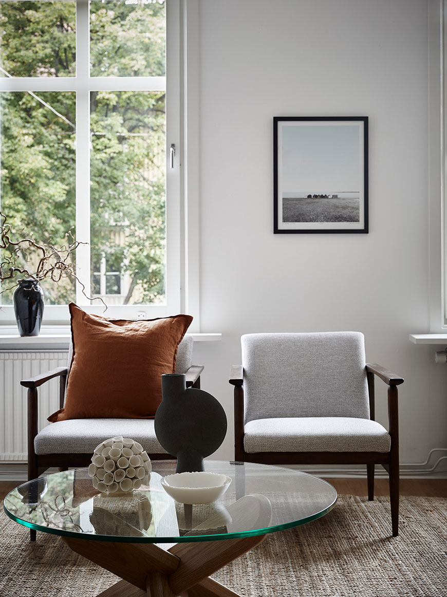 Two grey Mid-Century chairs with a rusty coloured linen cushion and ceramic vases on a glass coffee table.
