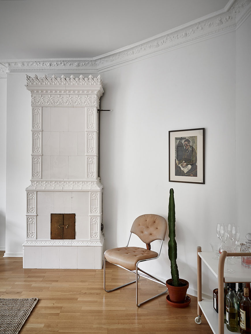 White tiled Swedish fireplace and bar cart in the living room of a Gothenburg apartment.
