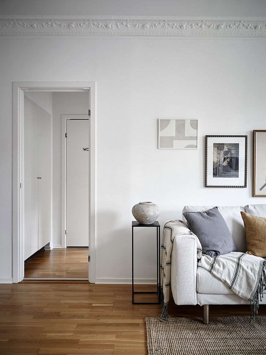 Looking into the bedroom from the living room with white sofa and parquet wood floors.
