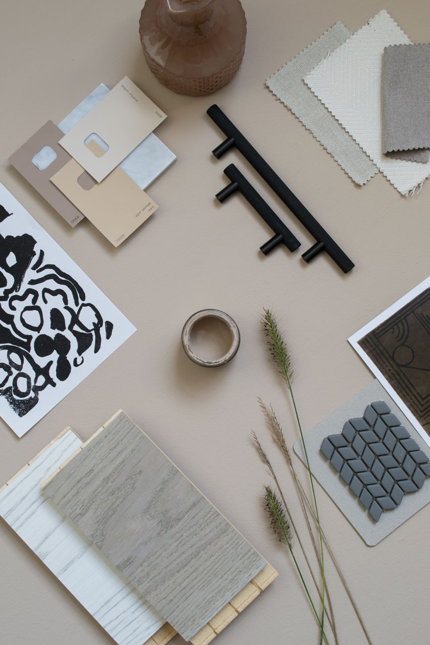 Flatlay mooboard with floor sample, grasses and black metal cupboard handles for a beige bedroom scheme.