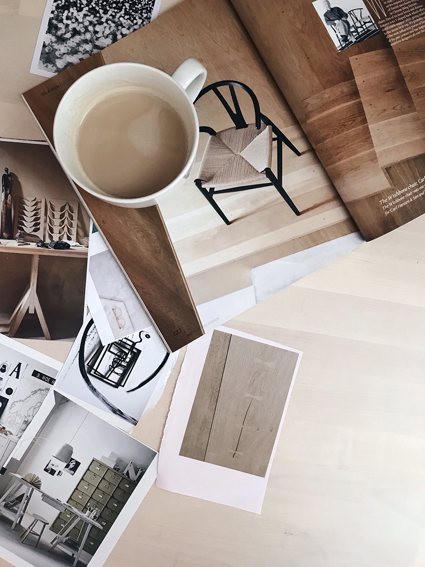 a white coffee cup on a birch wood table with magazine cuttings for a moodboard