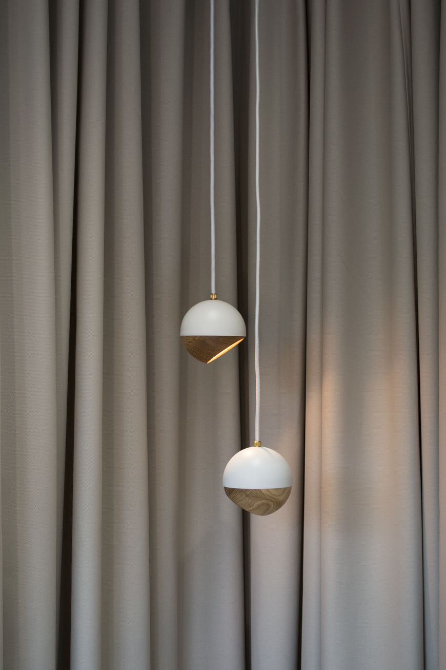 Two white and oak Ray pendant lamps against a grey curtain at Mater Gallery, Clerkenwell.