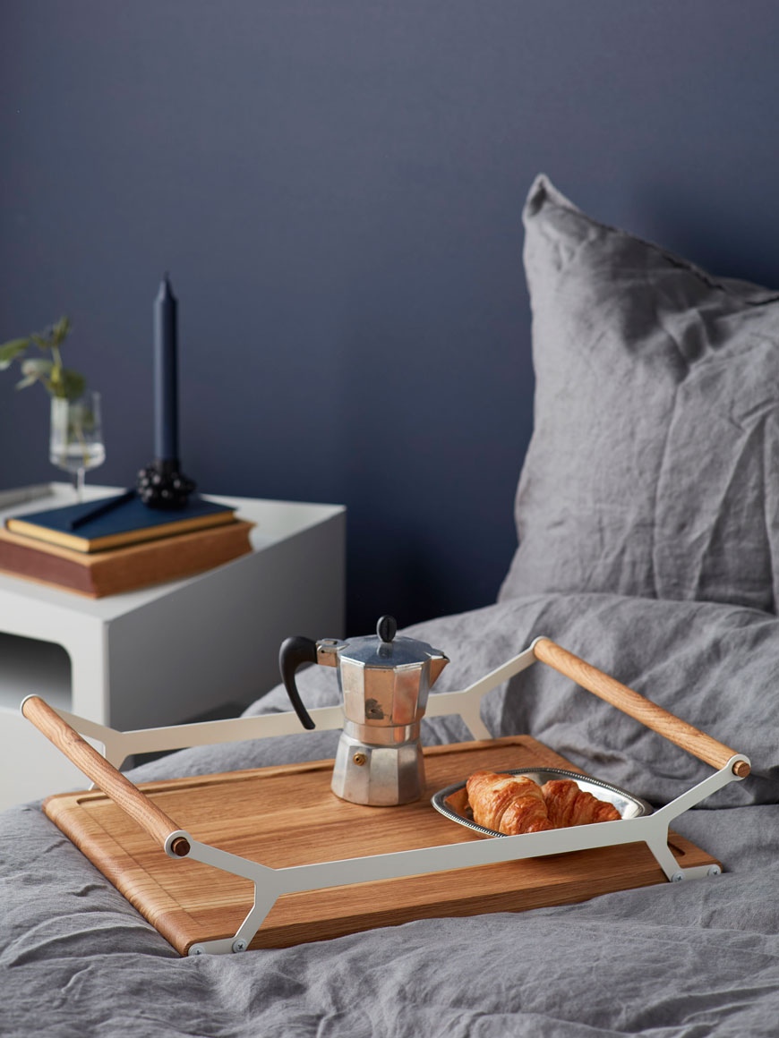 Breakfast in bed with a wooden tray in a cosy blue bedroom, by Nordic design brand Gejst