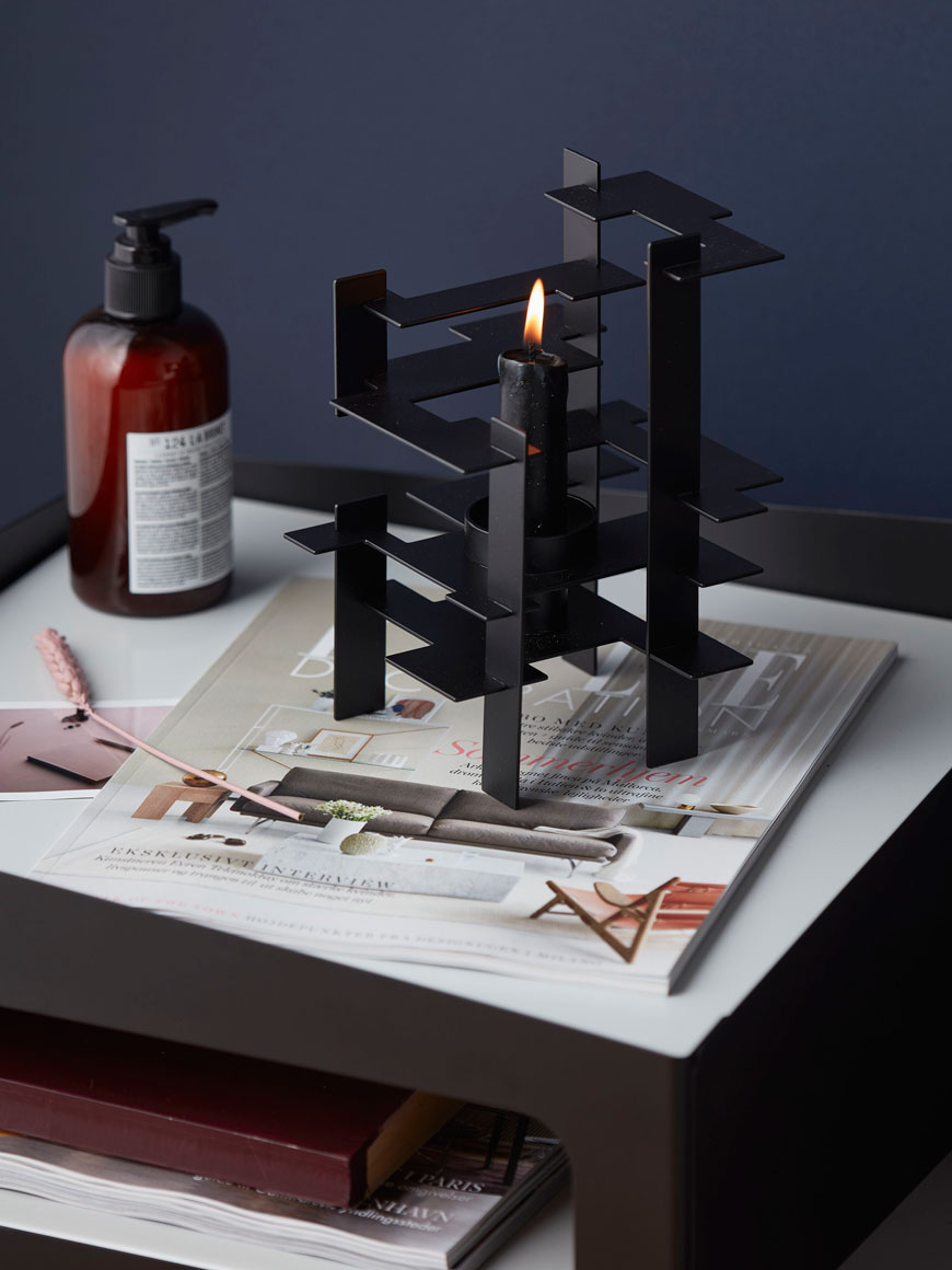 black metal candle holder styled on a cosy bedside table, designed by Nordic design brand Gejst