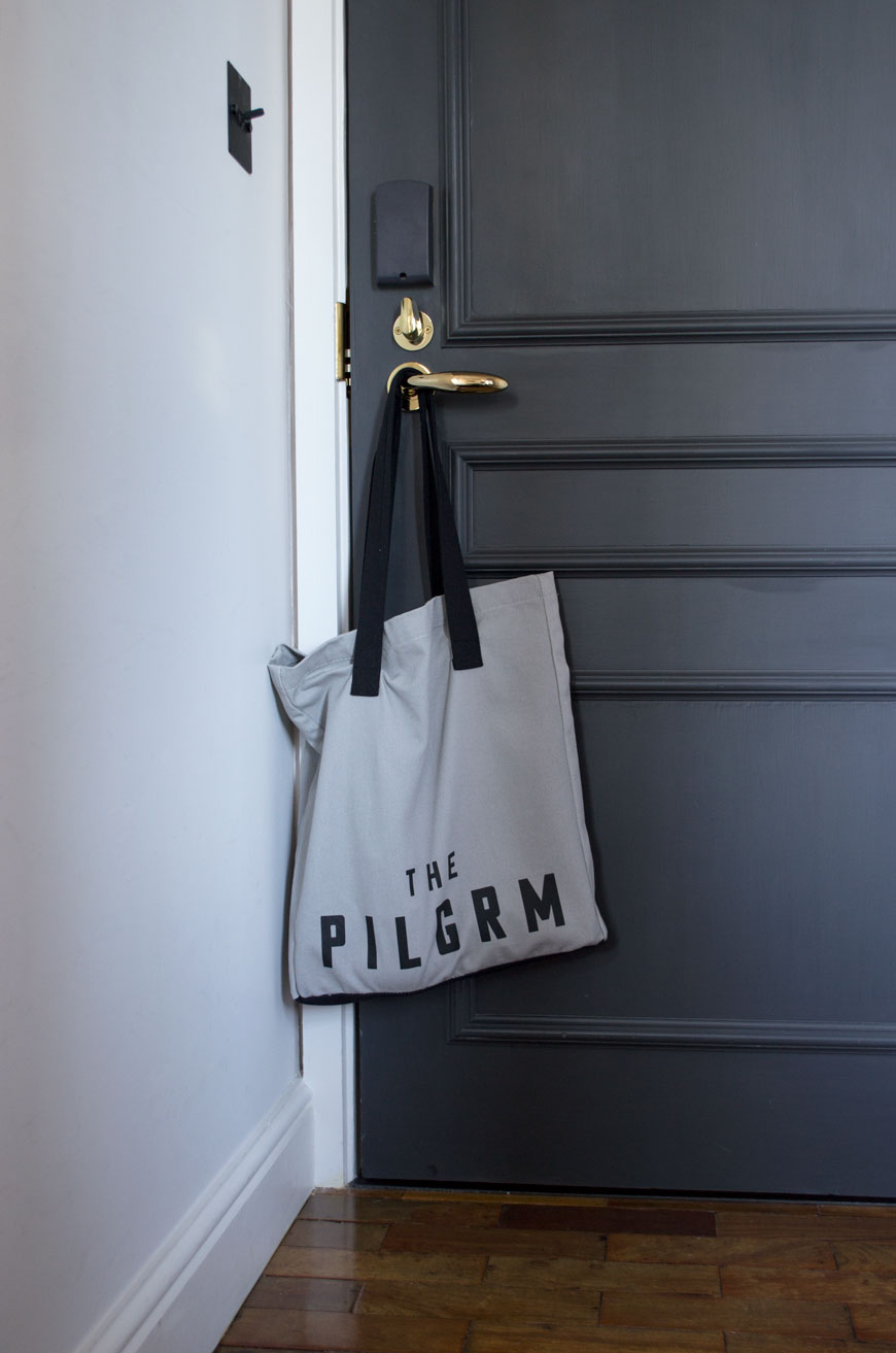 Custom The Pilgrm tote bag hanging on the door inside the bedroom.