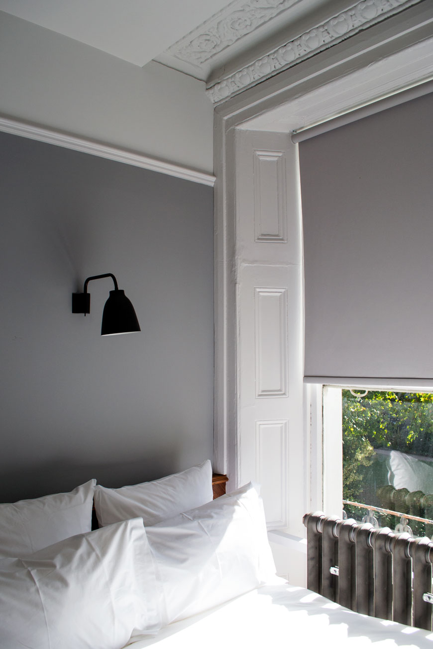 Grey and white Victorian bedroom with black wall lamp at The Pilgrm Hotel