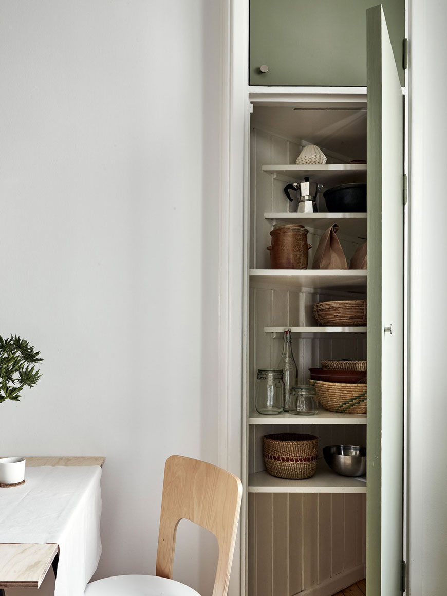 A corner storage cupboard in a kitchen with green kitchen units.