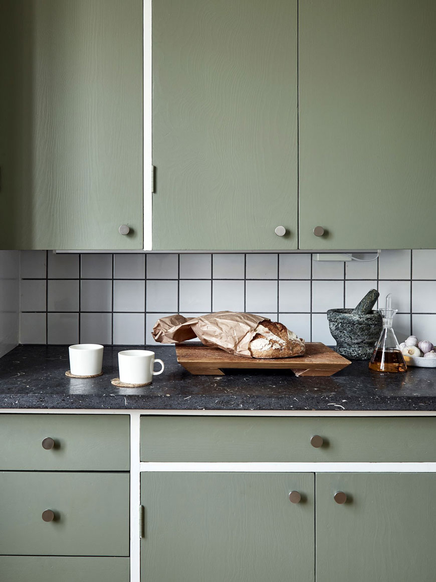 Coffee and toast on the slate worktop in this apartment with green kitchen units.