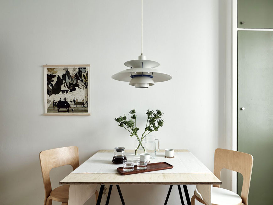 a table for two in a sweet little Gothenburg apartment with green kitchen units.