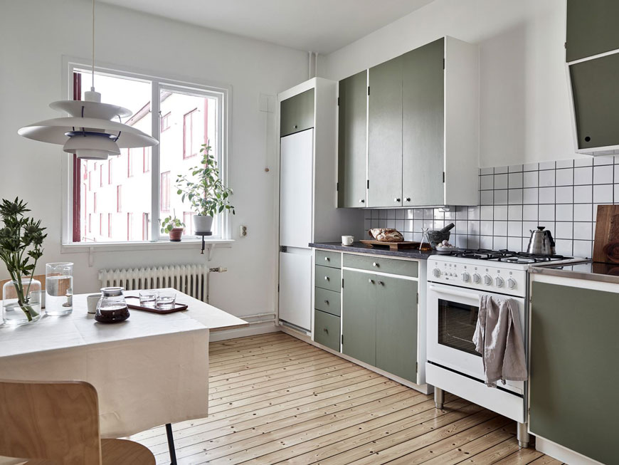 Inside a warm and inviting Gothenburg apartment with green kitchen units.