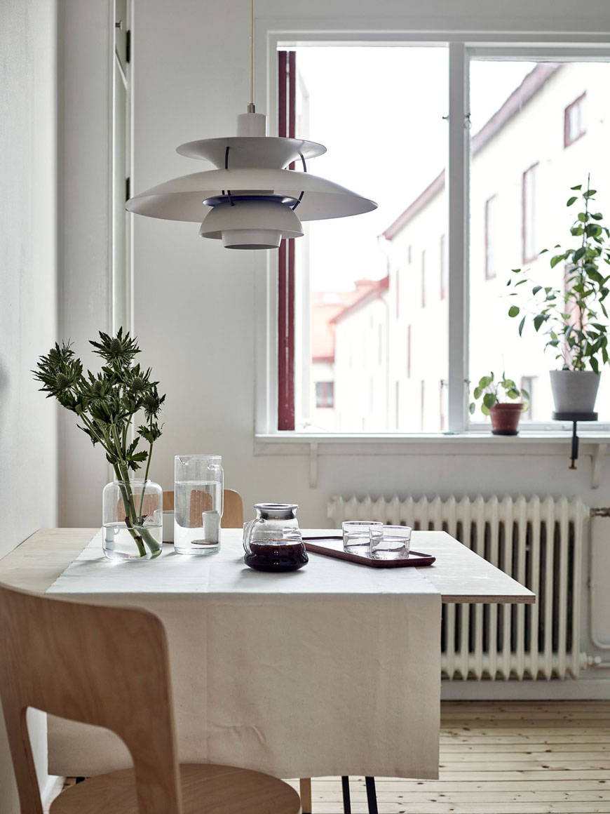 The PH 5 pendant lamp by Louis Poulsen sits over the kitchen table in a Gothenburg apartment.