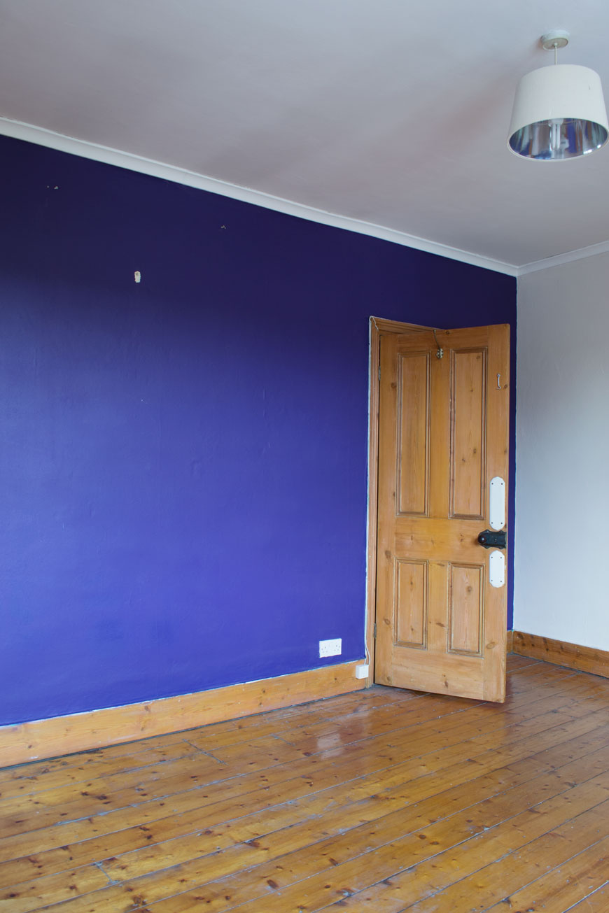 A deep purple feature wall and orange pine floorboards before our Nordic luxe bedroom makeover