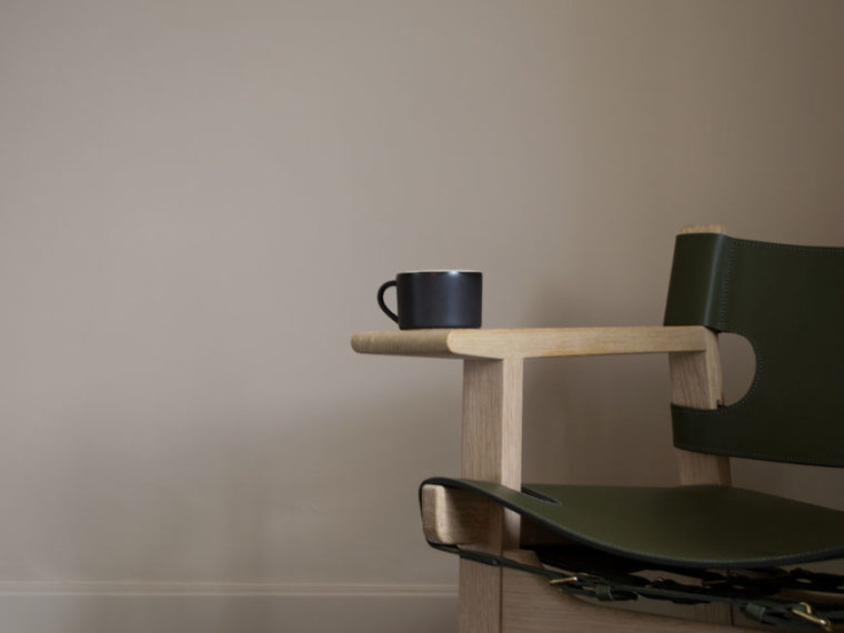 A black mug sits on the wide arms of The Spanish Chair, produced by Fredericia.