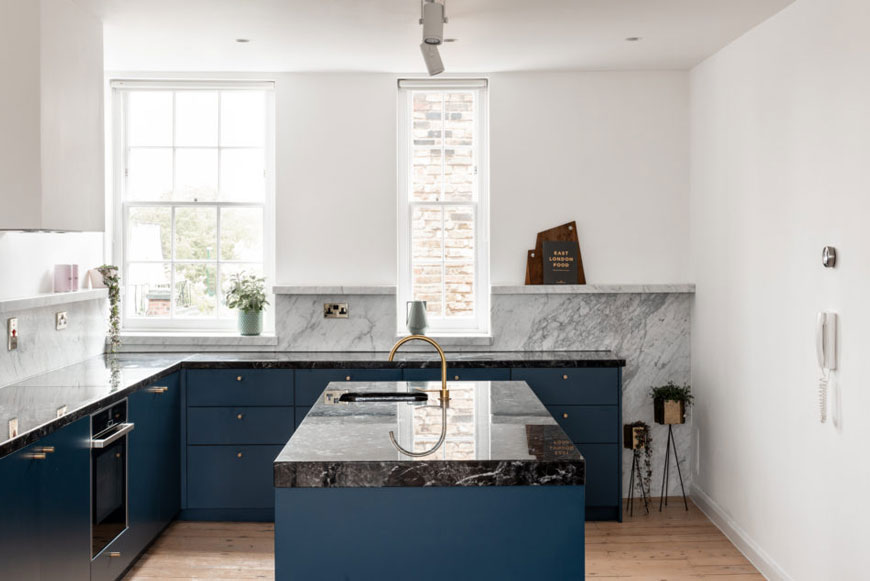 A blue kitchen with grey marble backsplash in a Hackney home in London.