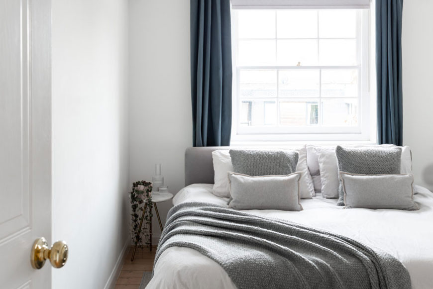 A Scandinavian styled bedroom with grey and white bedding and blue curtains in a Hackney home.