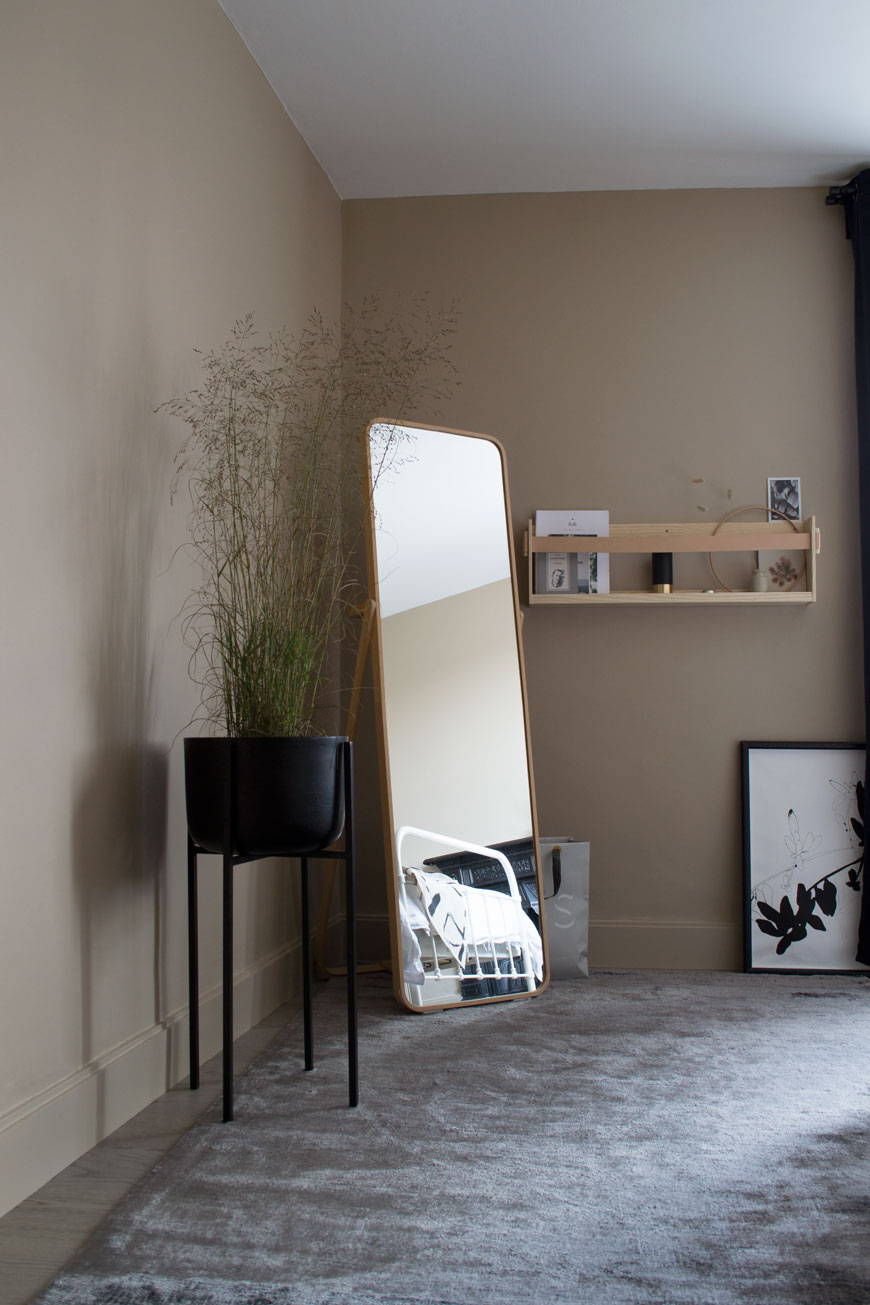 Looking into the bedroom with a light grey rug, floor length mirror and Nordic luxe look.