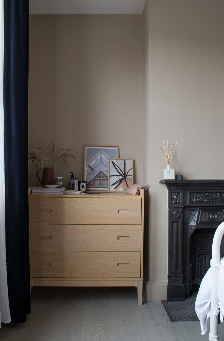 An oak chest of drawers in a beige bedroom with a Nordic luxe style.