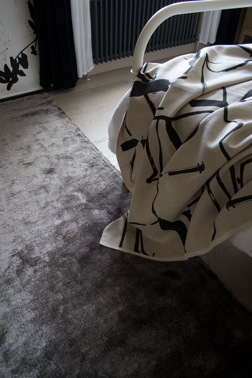 Looking onto a grey rug and an abstract art style bed throw inside a Nordic luxe style bedroom.