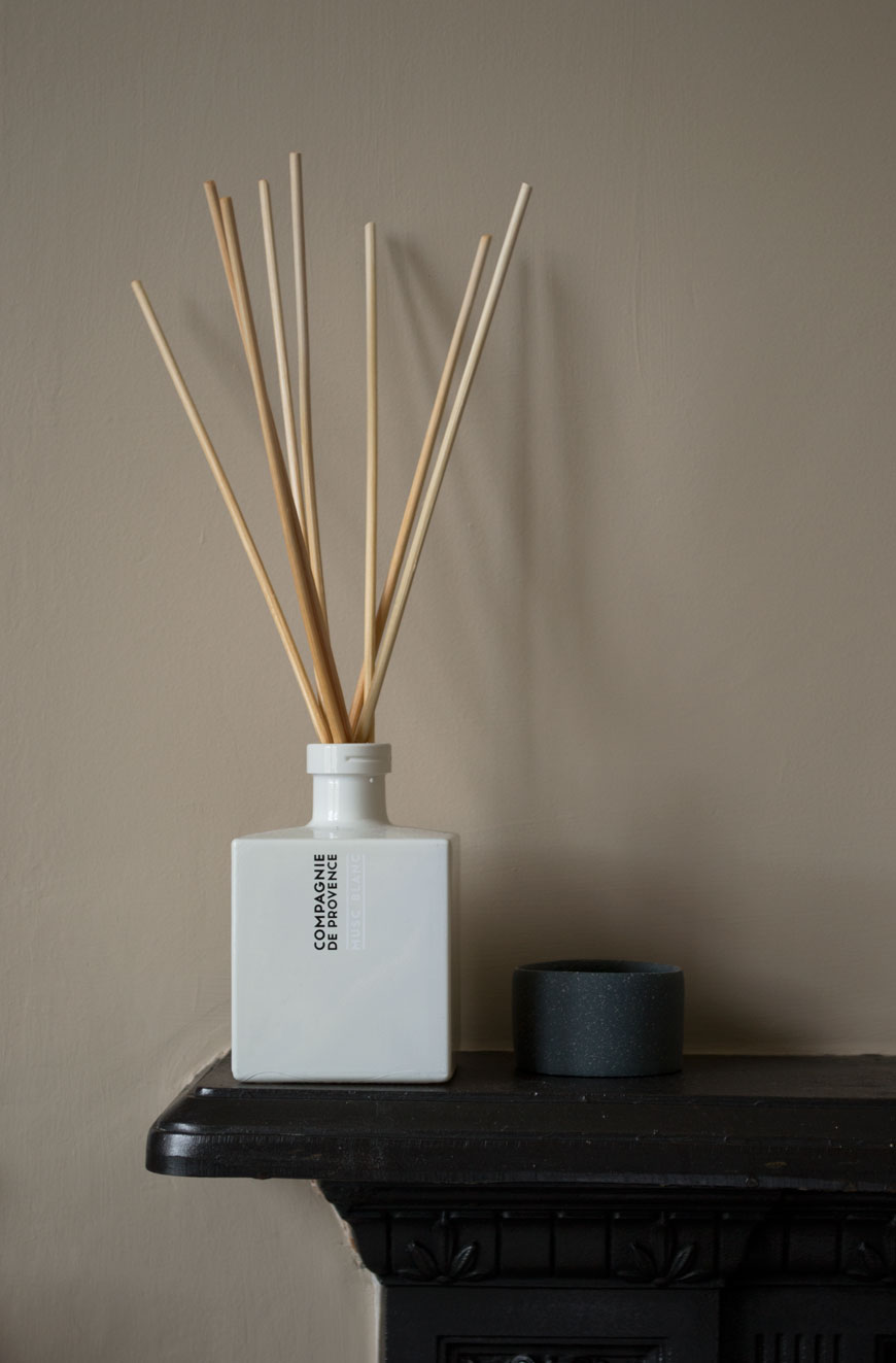 A white room diffuser and sweet little ceramic pot in a beige bedroom with Nordic luxe style.