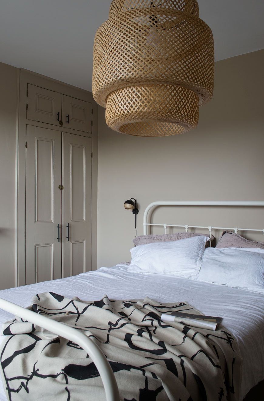 A white metal hospital style bed inside a beige bedroom with a bamboo lamp shade with Nordic luxe style.
