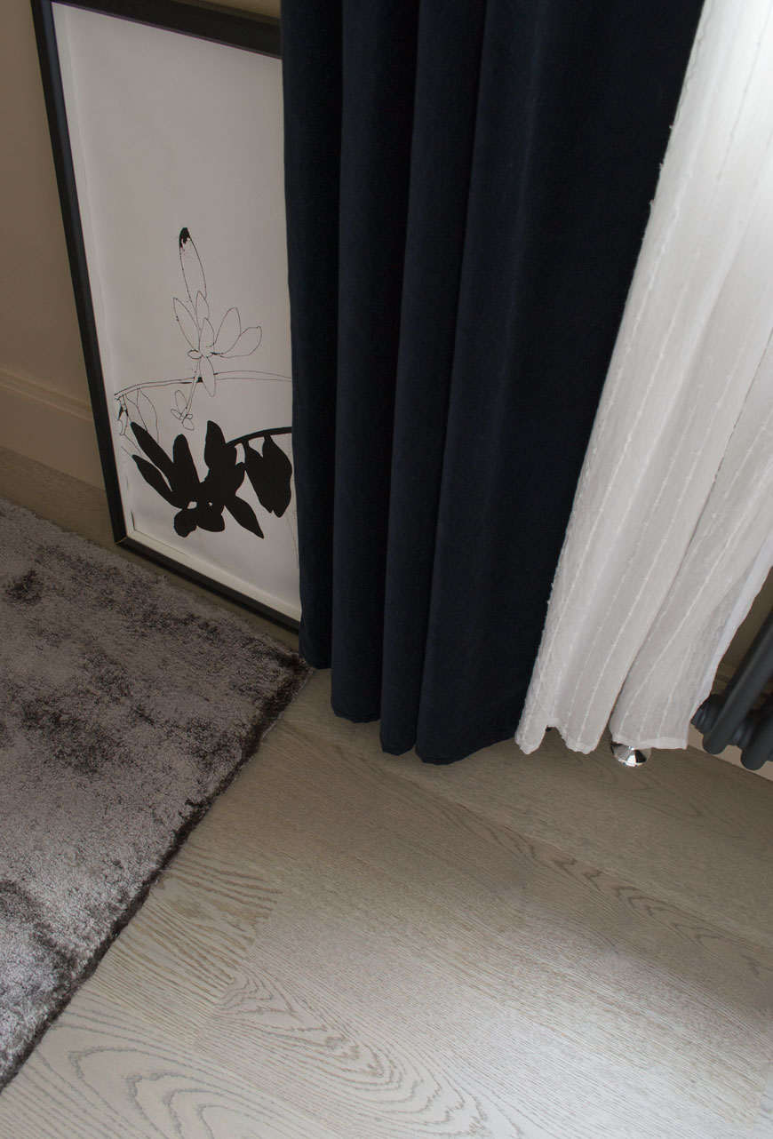 Grey oak floorboards look luxurious against the thick grey rug and velvet curtain in a Nordic luxe bedroom