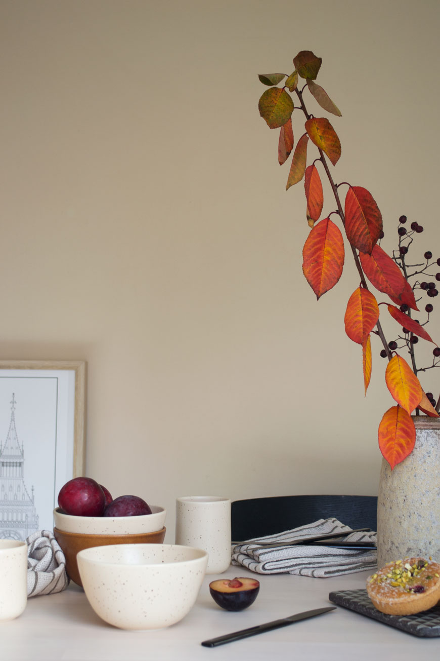 how to style your home for winter using rusty orange autumn leaves styled in a vase on the dining table with tableware from NABO