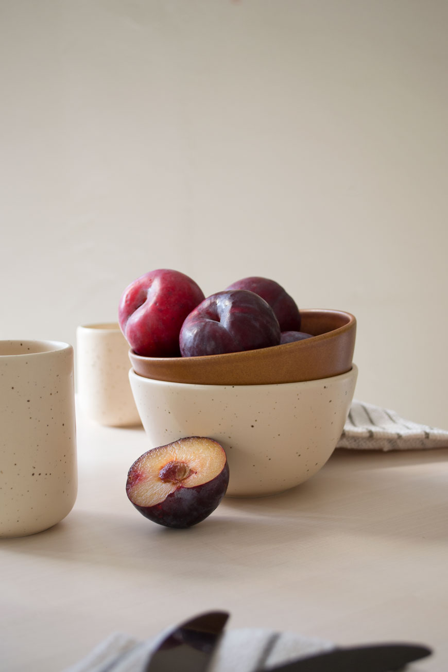 A bowl of plums styled in a stack of bowls, made in Denmark for NABO shop.